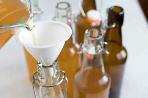 use a small funnel to pour the finished kombucha into swing top bottles