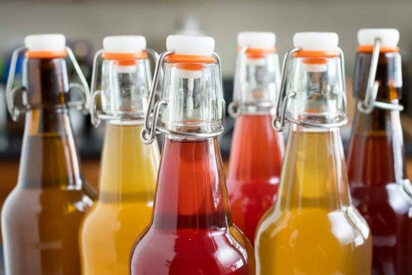 Side view of several bottles filled with kombucha