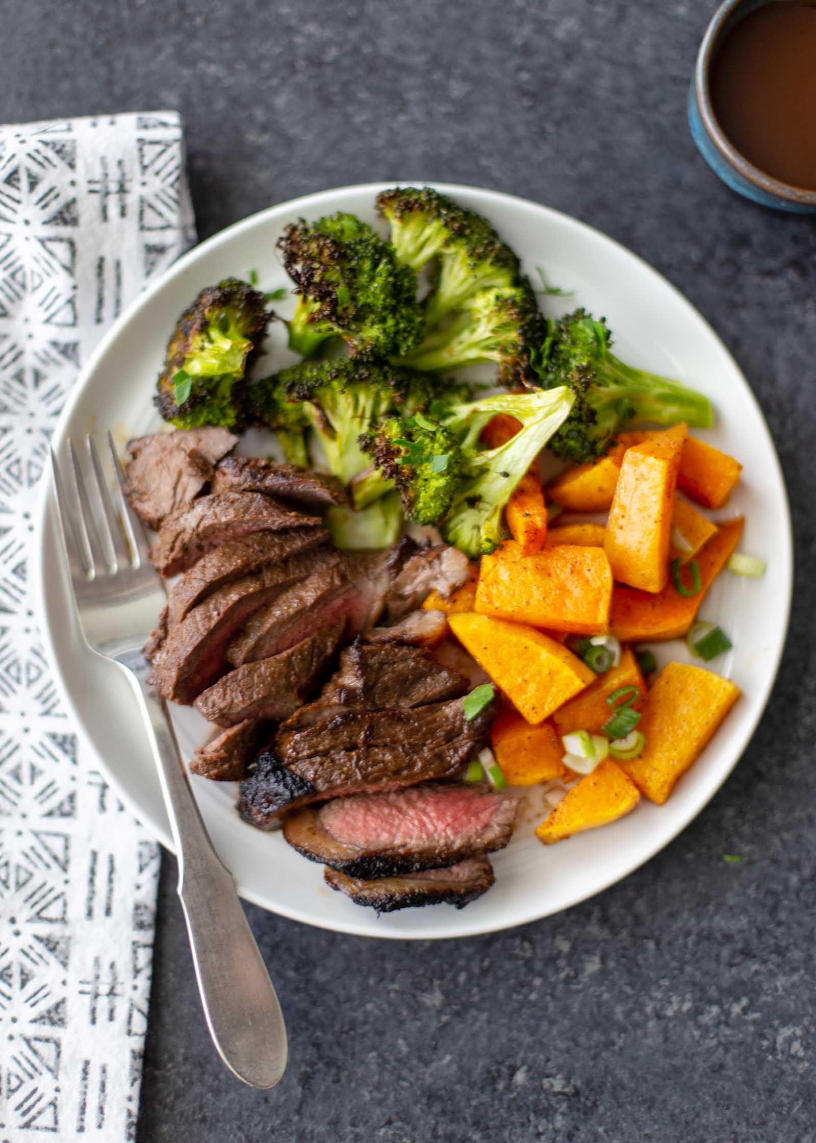 Sliced oven broiled steak on a white plate with seared edges and pink middle. Roasted broccoli and squash are on the plate.