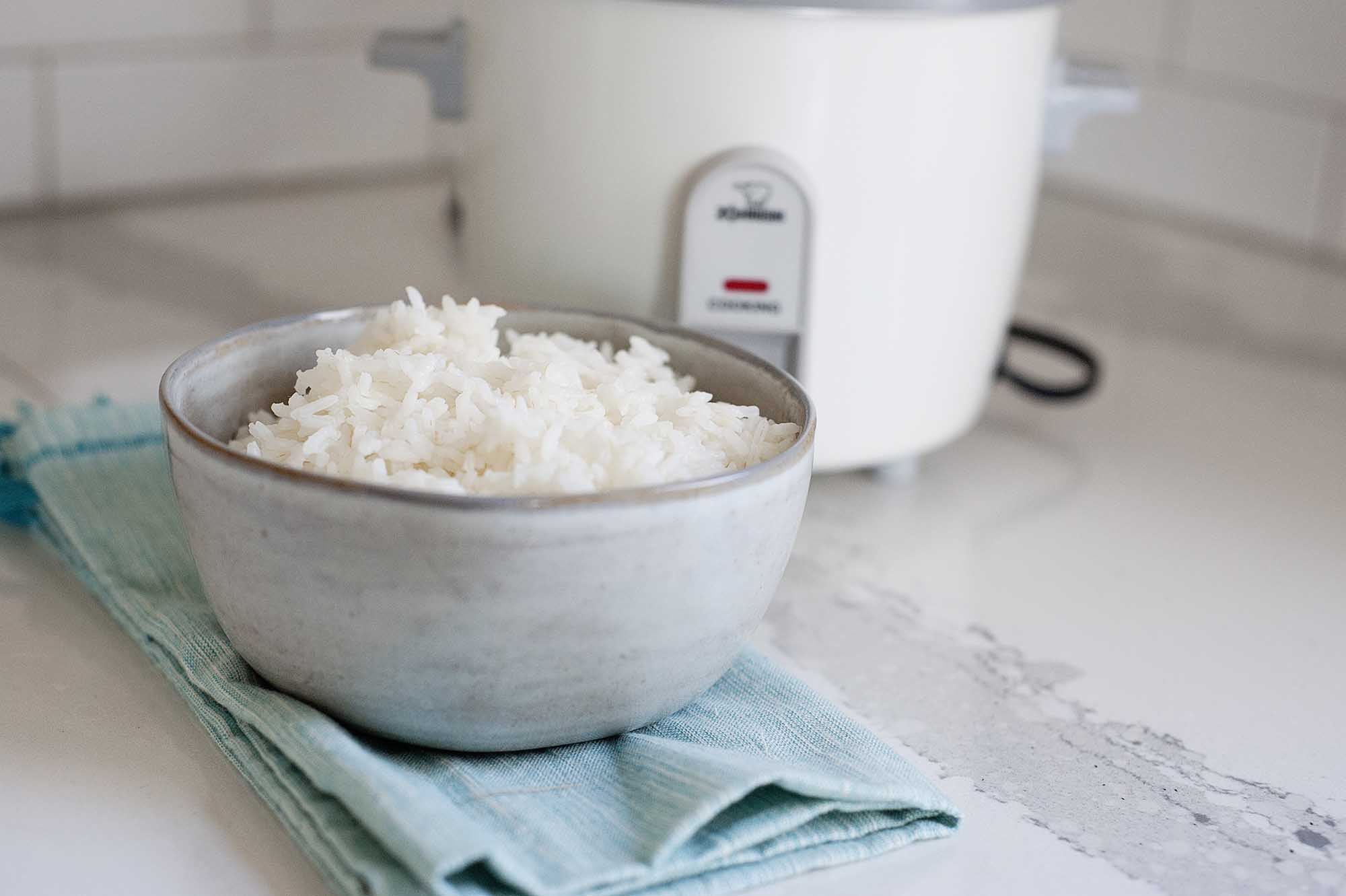 Horizontal image of a ceramic bowl filled with white rice on a white counter. A teal dish towel is under the bowl of rice and a white rice cooker is in partial view behind the bowl.