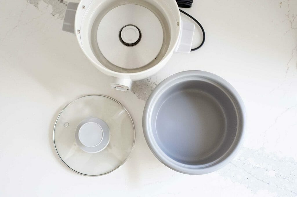 Overhead view of the three main parts of a rice cooker. The outer heating appliance, inner bowl and lid are in a triangle pattern on a white counter.