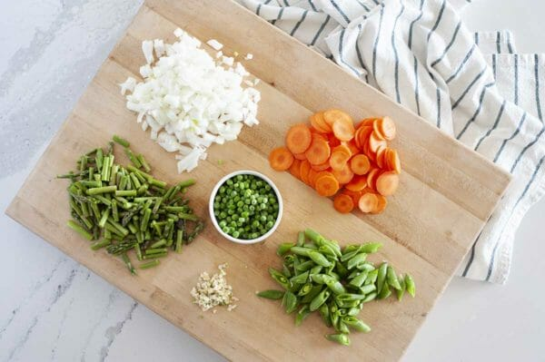 Cutting board with piles of chopped ingredients for vegetarian soup with pesto. Onion, carrot, asparagus, peas, snap peas and garlic on on the board and a blue striped dish towel is to the right.