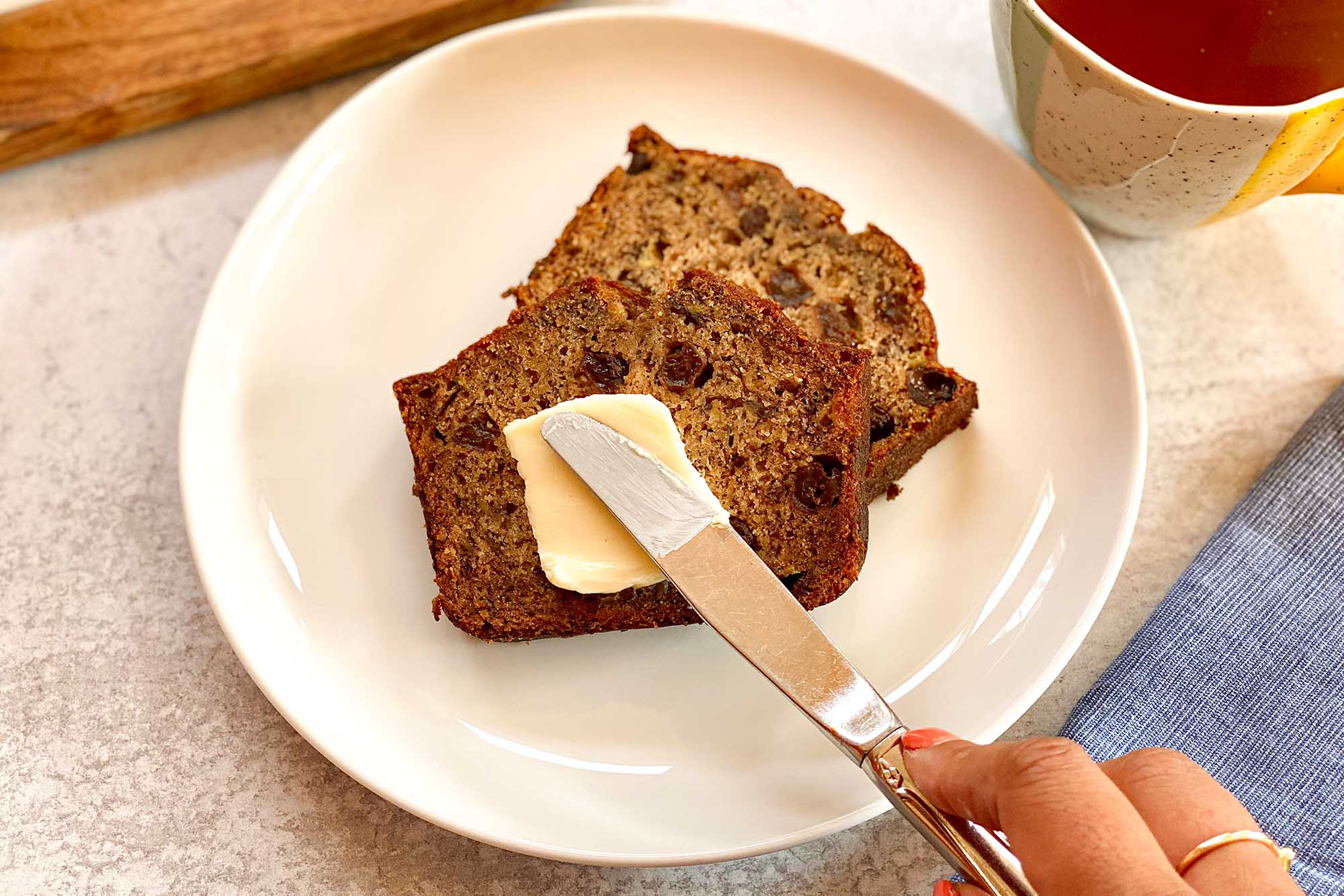 Two slices of rum raisin banana bread on a plate and getting butter spread on top.