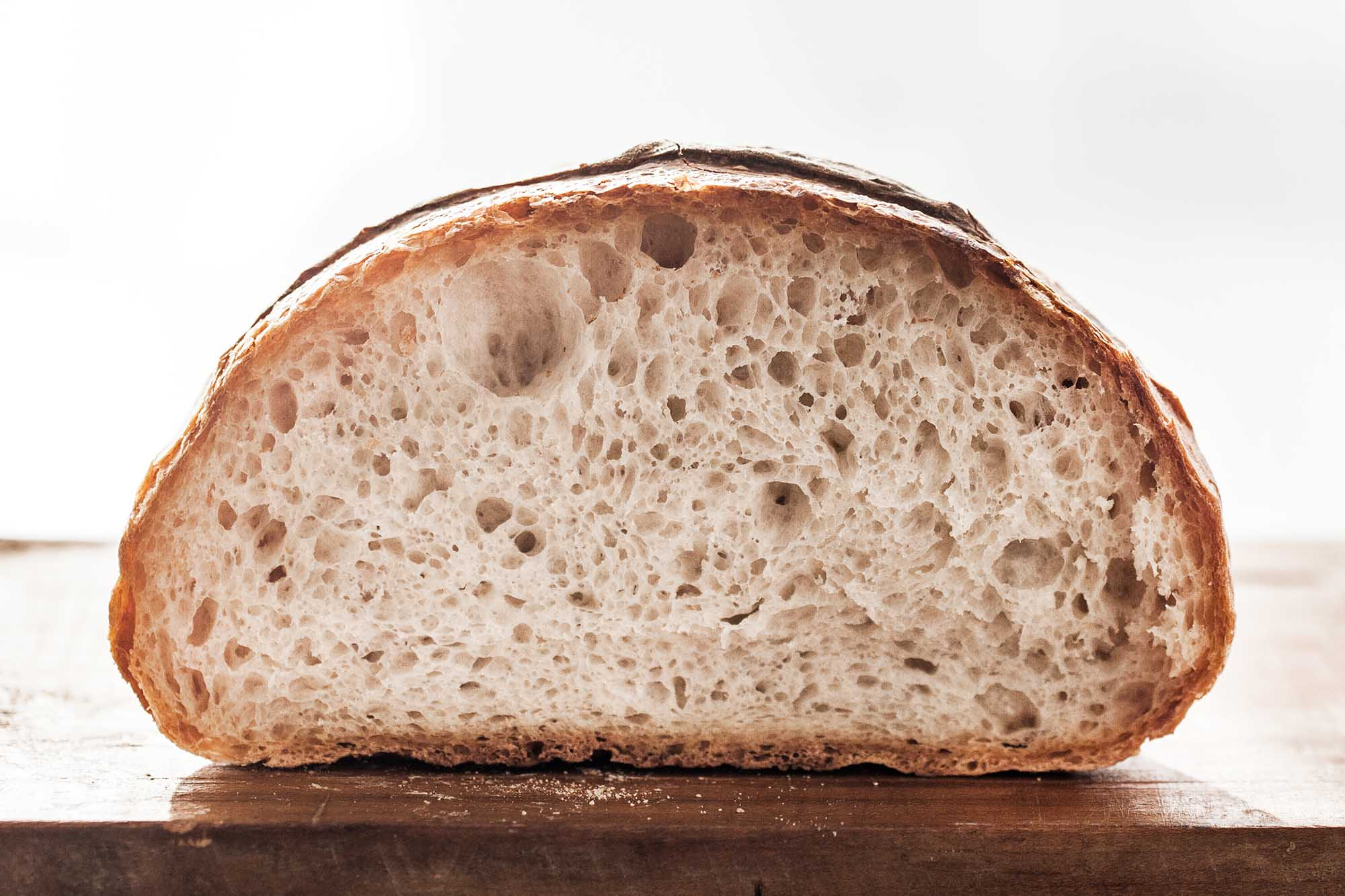Easy kno knead bread is on a wooden cutting board and the the inside of the crusty loaf is visible.