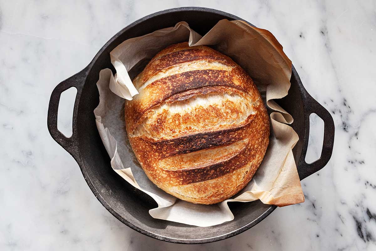 Showing How to Make No Knead Bread in a dutch oven. The loaf is golden and crusty inside the pot and has browned parchment paper underneath the loaf..