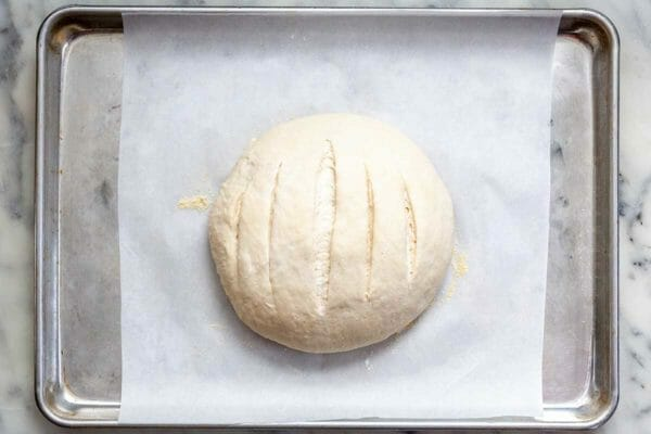 No-Knead Dutch Oven Bread on a parchment covered baking sheet with the slits in the top of the dough.