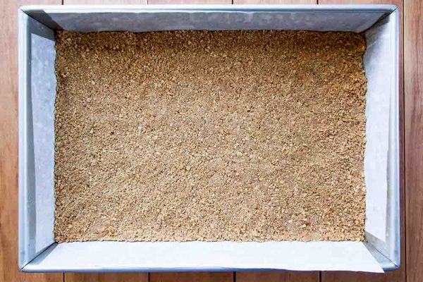 Graham cracker layer for magic bars pressed into the baking dish