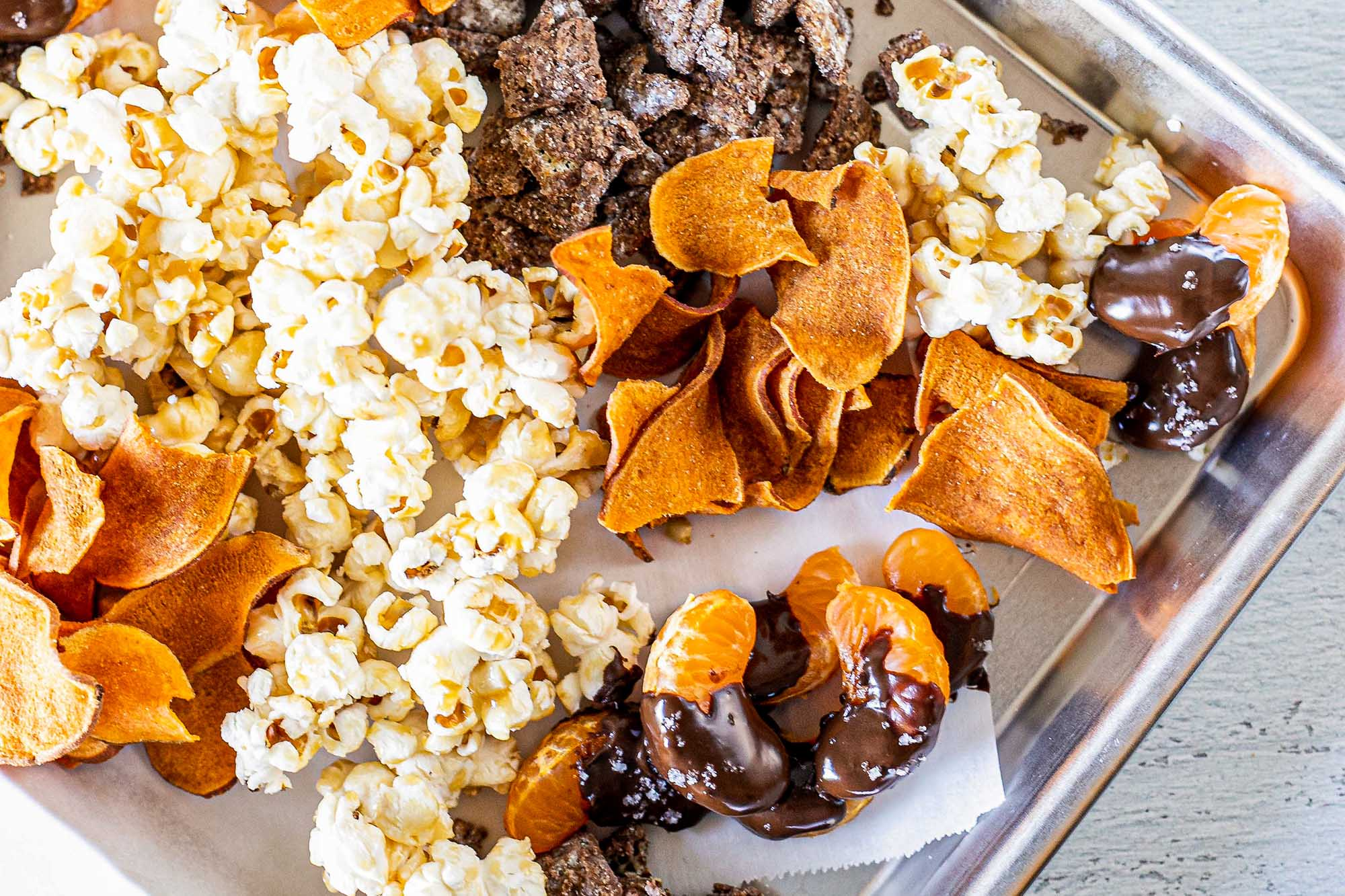 Kids lunch ideas with popcorn, chips and chocolate covered oranges on a baking tray.