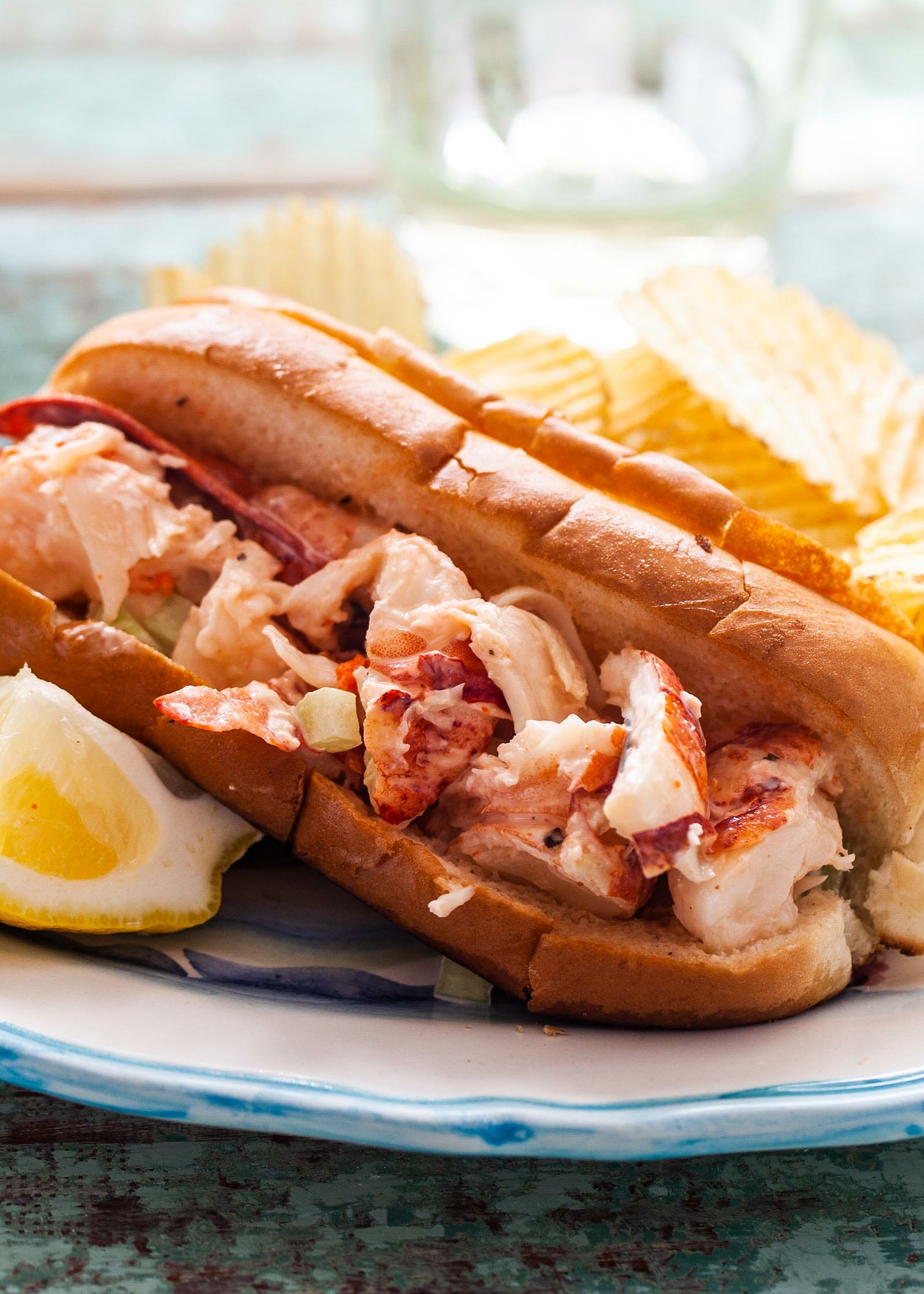 Side view of the best lobster roll recipe on a table. Lobster salad inside a toasted bun served with chips and lemon wedges. Glasses, plates and additional lobster salad are above the plate.