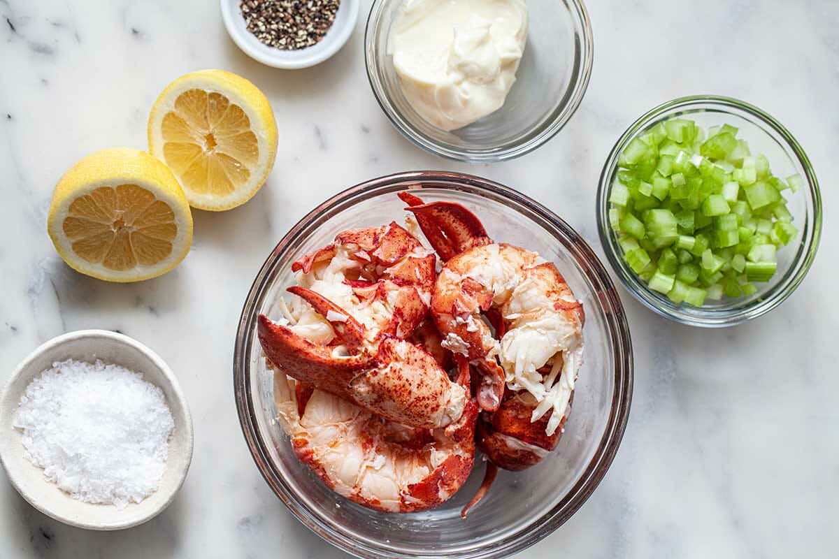 How to make lobster rolls with individual bowls of the lobster salad ingredients set on a table.