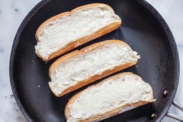 Three split rolls buttered and in a skillet to toast for a homemade lobster roll recipe.