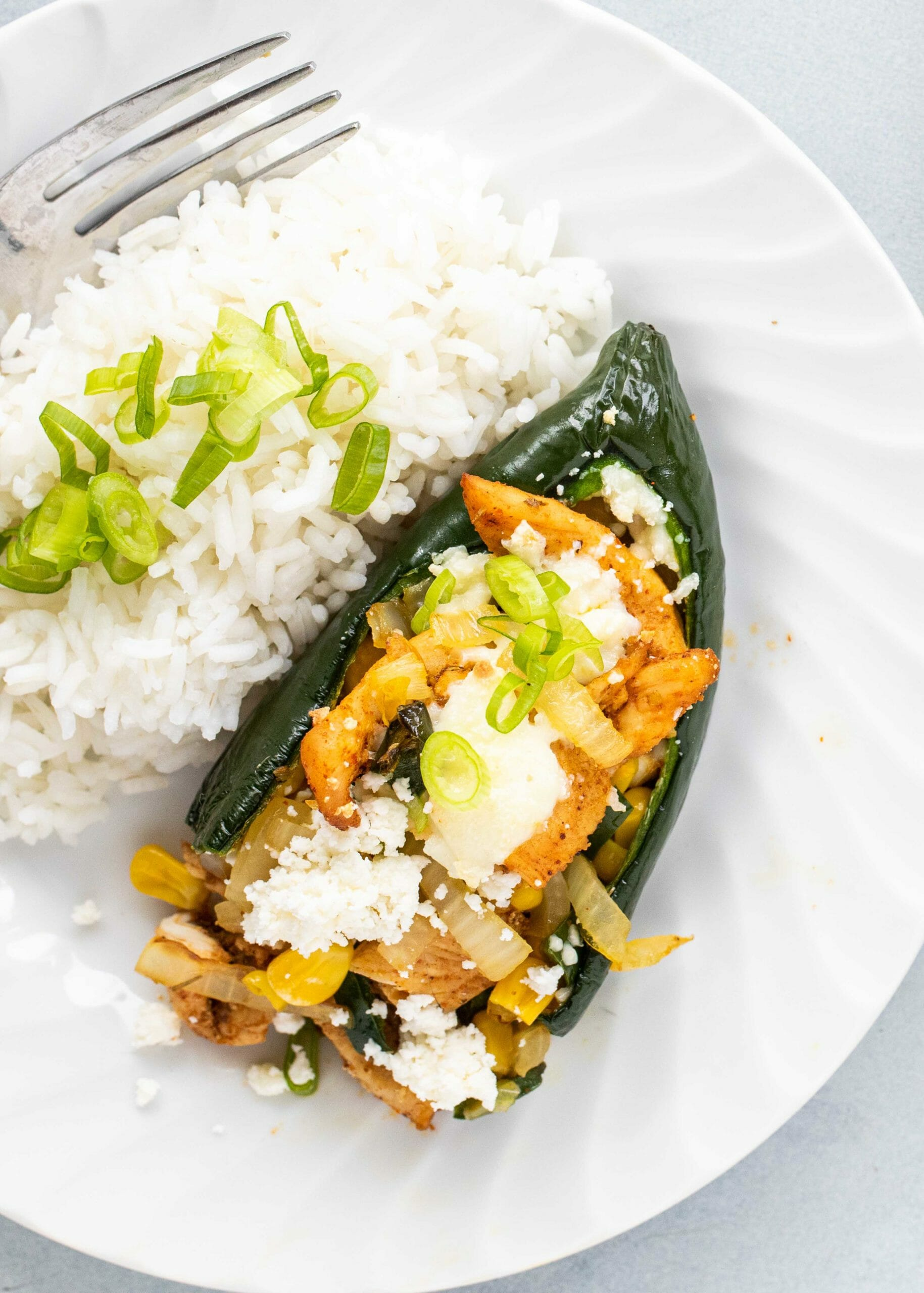 Mexican stuffed peppers with sliced chicken, onions and peppers inside a poblano pepper. A side of white rice and a fork are on the plate next to the pepper.
