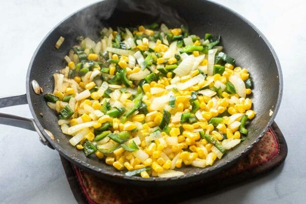 Low Carb Stuffed Pepper Recipe. A non-stick skillet has a filling of corn, onions and green peppers inside.