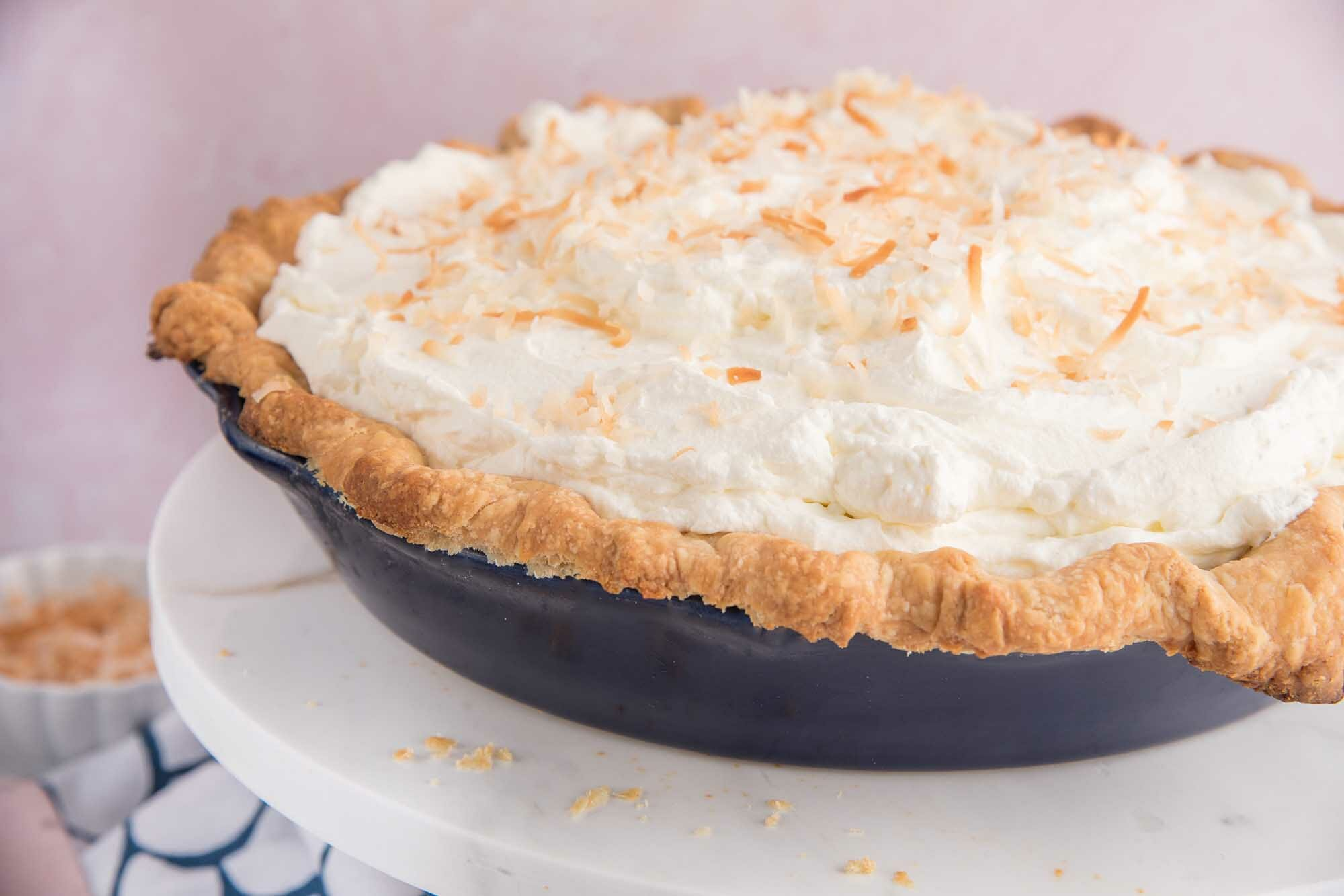 Side view of an easy coconut cream pie on a cake stand.