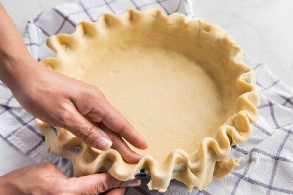 Pie dough is being crimped by two hands to show how to make coconut cream pie.