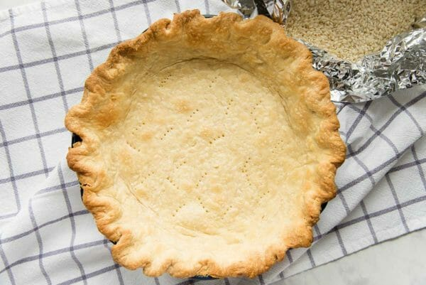 Blind baked pie crust on a checked linen for the best coconut cream pie.