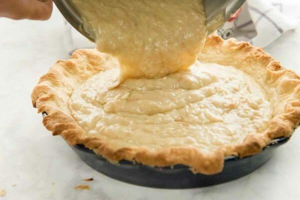 Coconut cream pie filling is being added to a baked pie crust for homemade coconut cream pie.