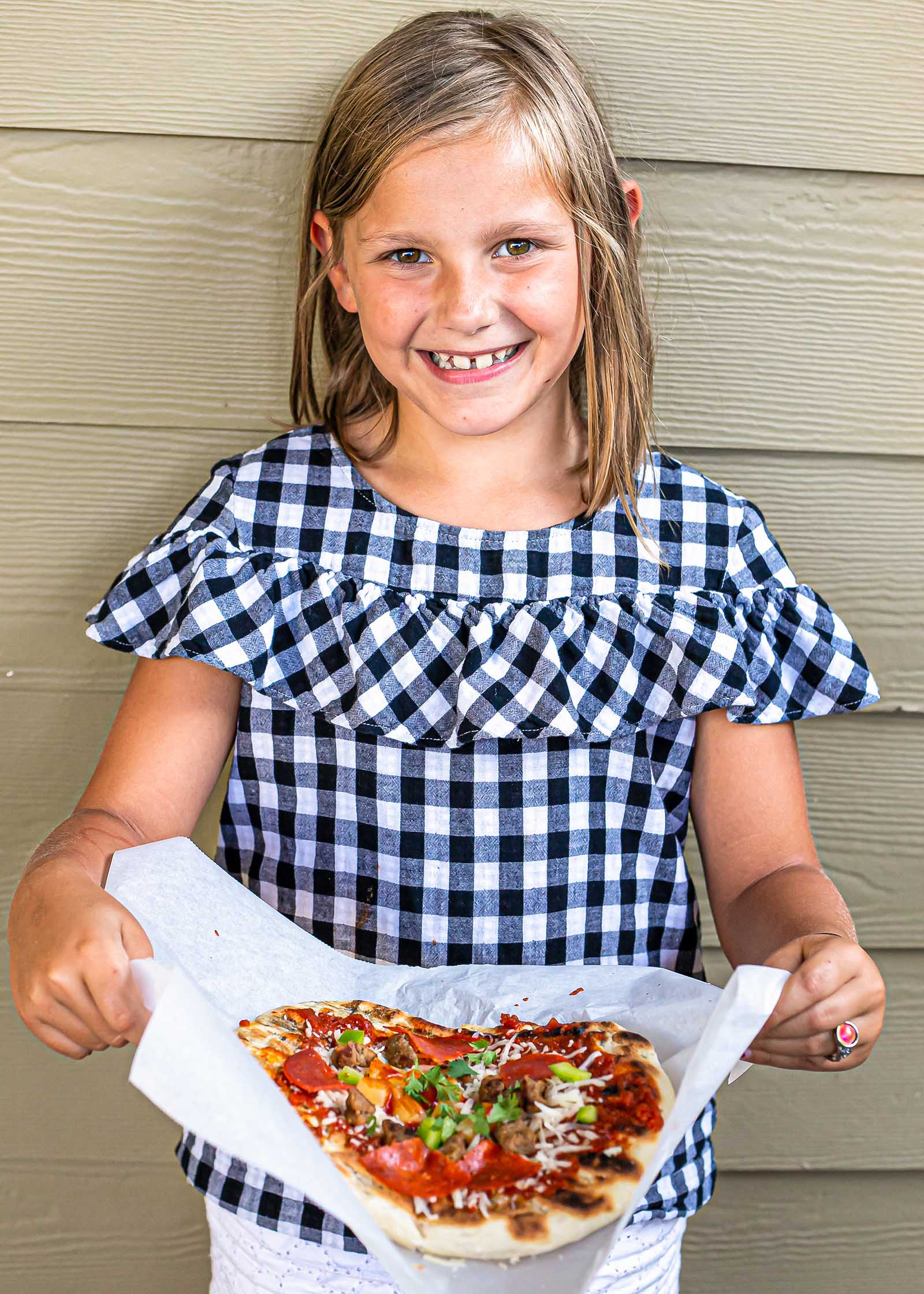How to grill pizza. A child holding a homemade pizza and smiling.