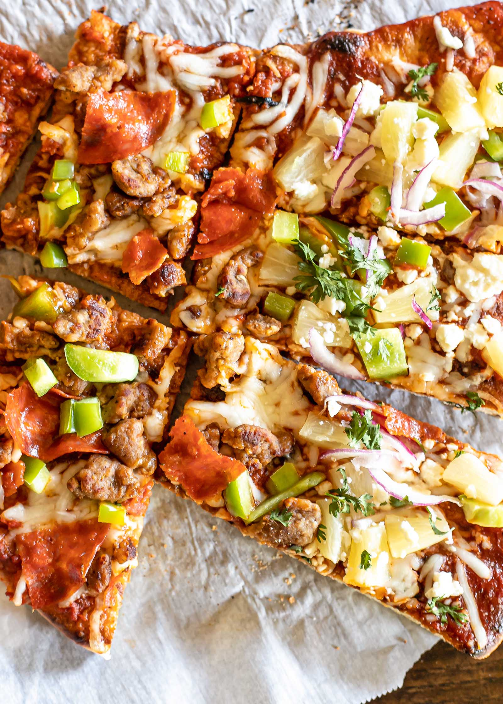 How to make pizza on the grill. Pizza sliced in rectangles and loaded with toppings.