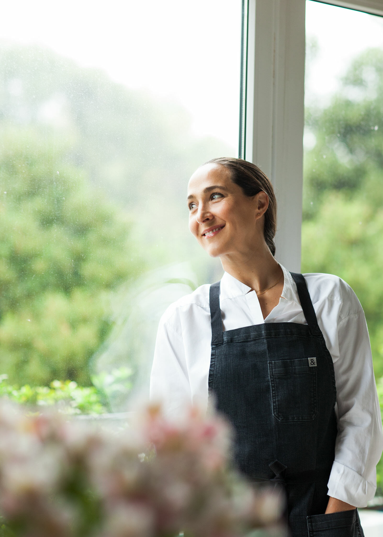 Author Gabriela Camara looking out the window and smiling.