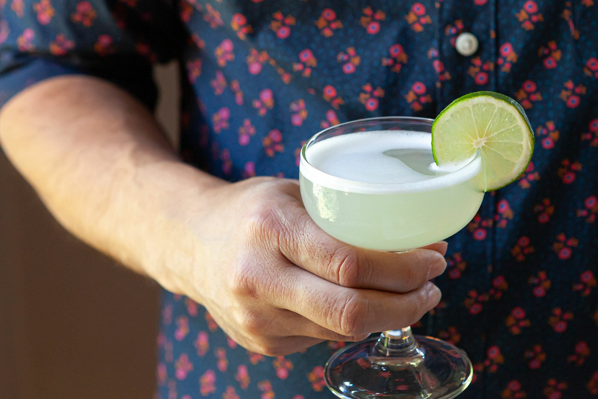 A person is holding a vodka gimlet in a chilled coupe with a lime wedge on the side.