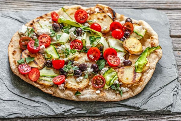 Grilled vegetable pizza topped with halved tomatoes, black olives, cheese, zucchini ribbons and sliced potatoes. The pizza is on a slate board.