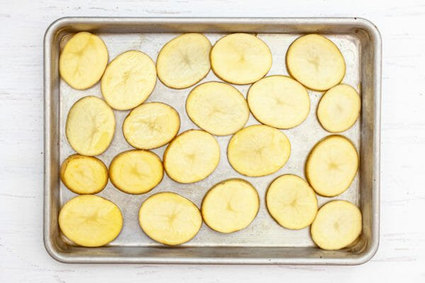 Yukon gold potatoes sliced into rounds and set on a baking sheet.