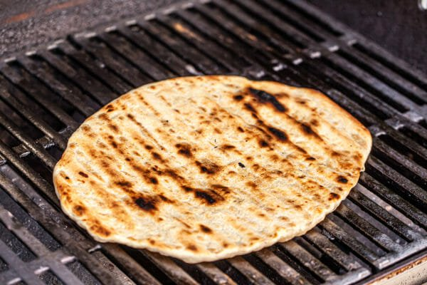 Crust for the best grilled pizza on the grill with grill lines and blackened parts visible.