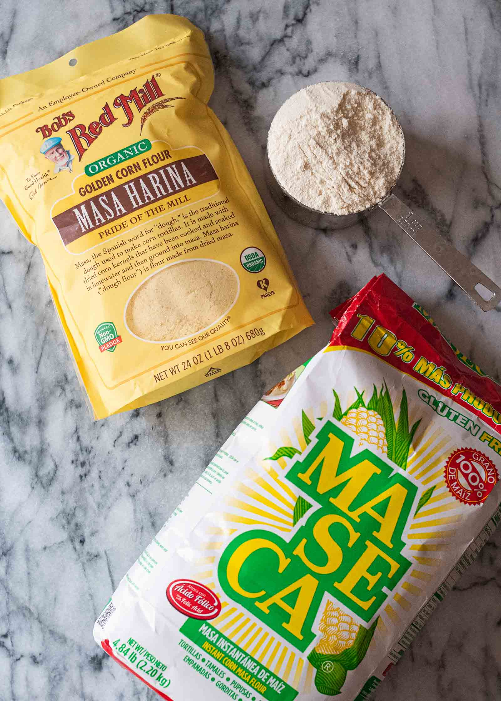 A bag of Bob's Red Mill Masa Harina and a bag of Maseca Instant Yellow Corn Flour. A measuring cup is filled with corn flour is in the upper right corner..