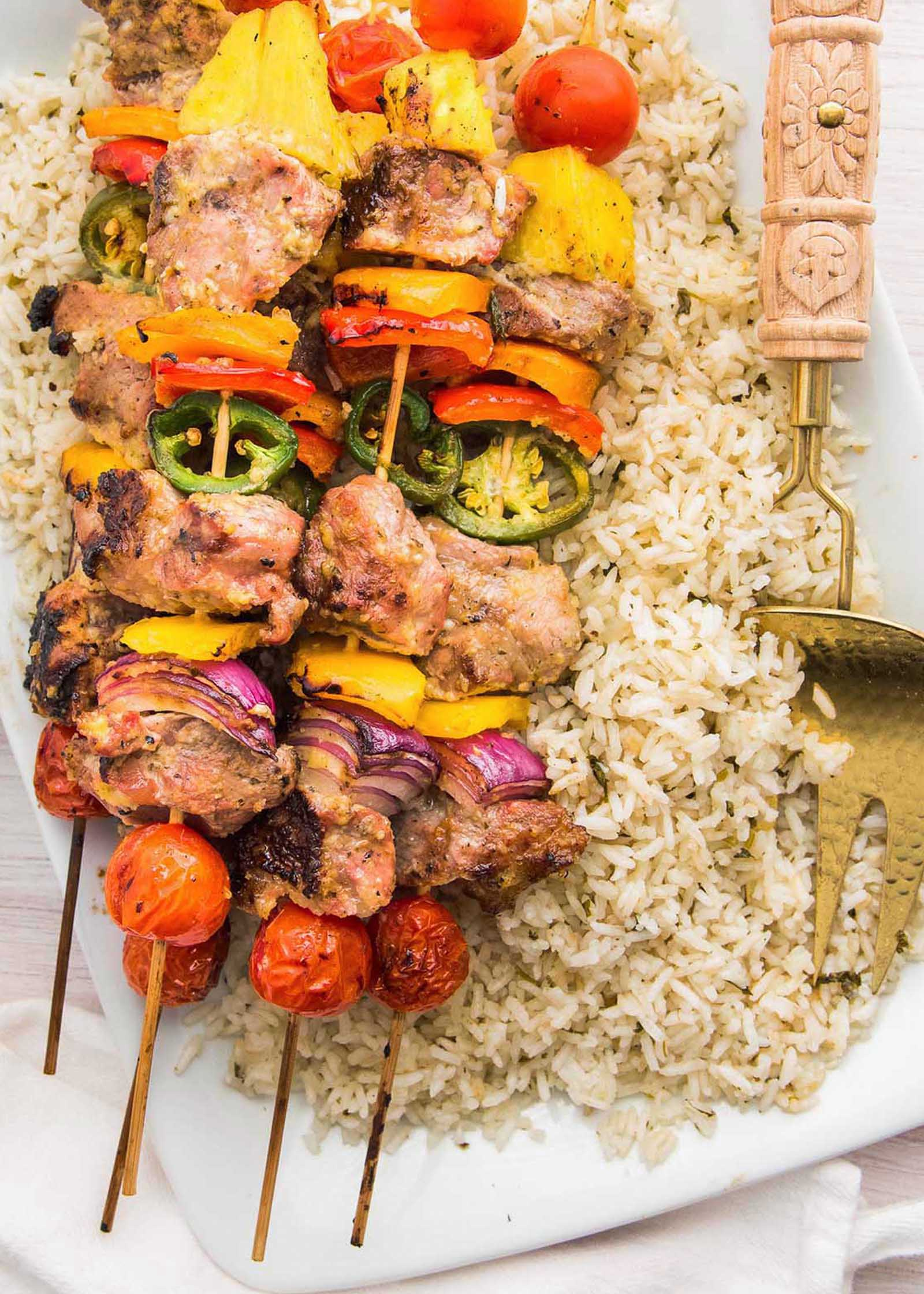 Garlic and citrus grilled pork kebabs are set over a bed of rice.