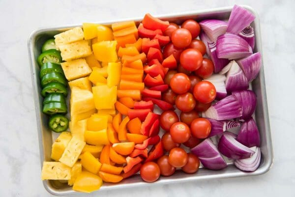 A rainbow of chopped vegetables are lined up on a quarter sheet pan to make easy grilled pork kebabs with mojo marinade.