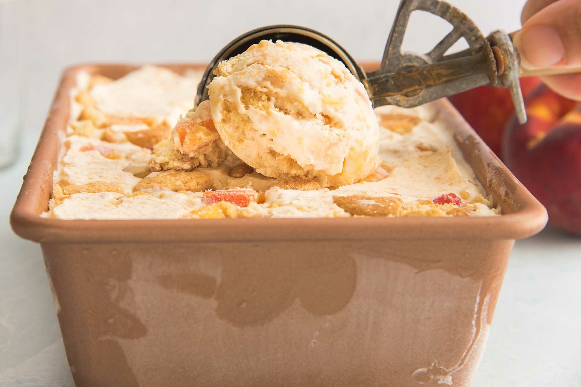 Peach cobbler ice cream is being scooped and chopped peaches are visible.