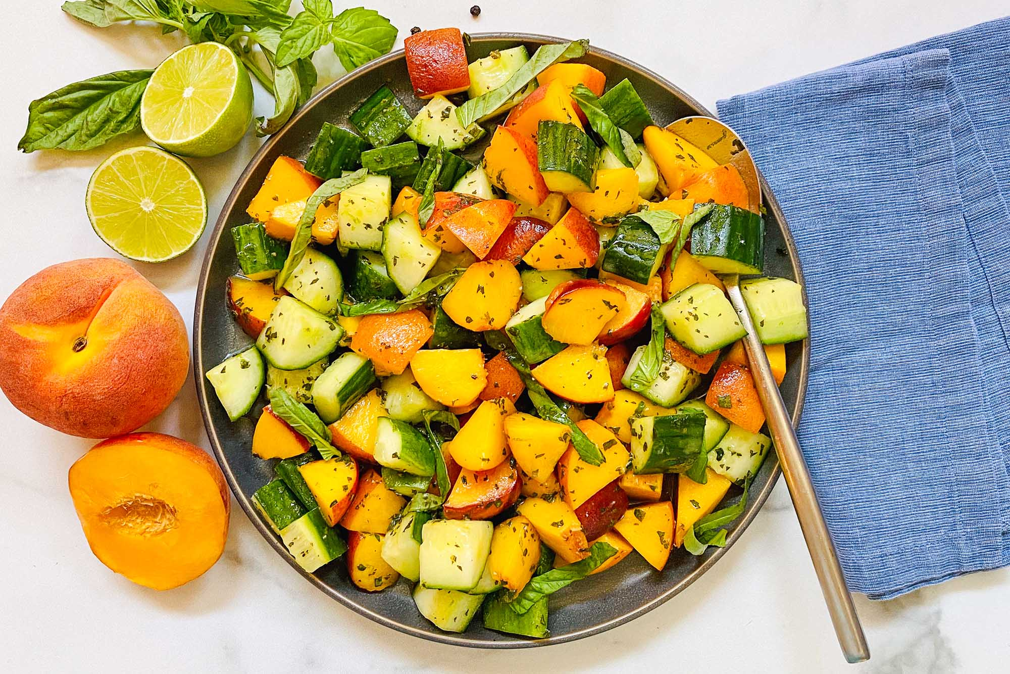 Summer peach and cucumber salad in a bowl with a serving spoon. A blue linen is to the right and peaches, limes and basil are to the left of the bowl.