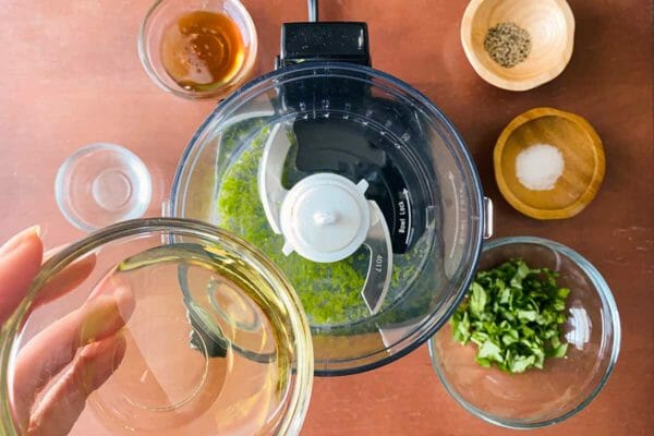 Ingredients for black pepper basil vinaigrette are being poured into the bowl of a food processor.