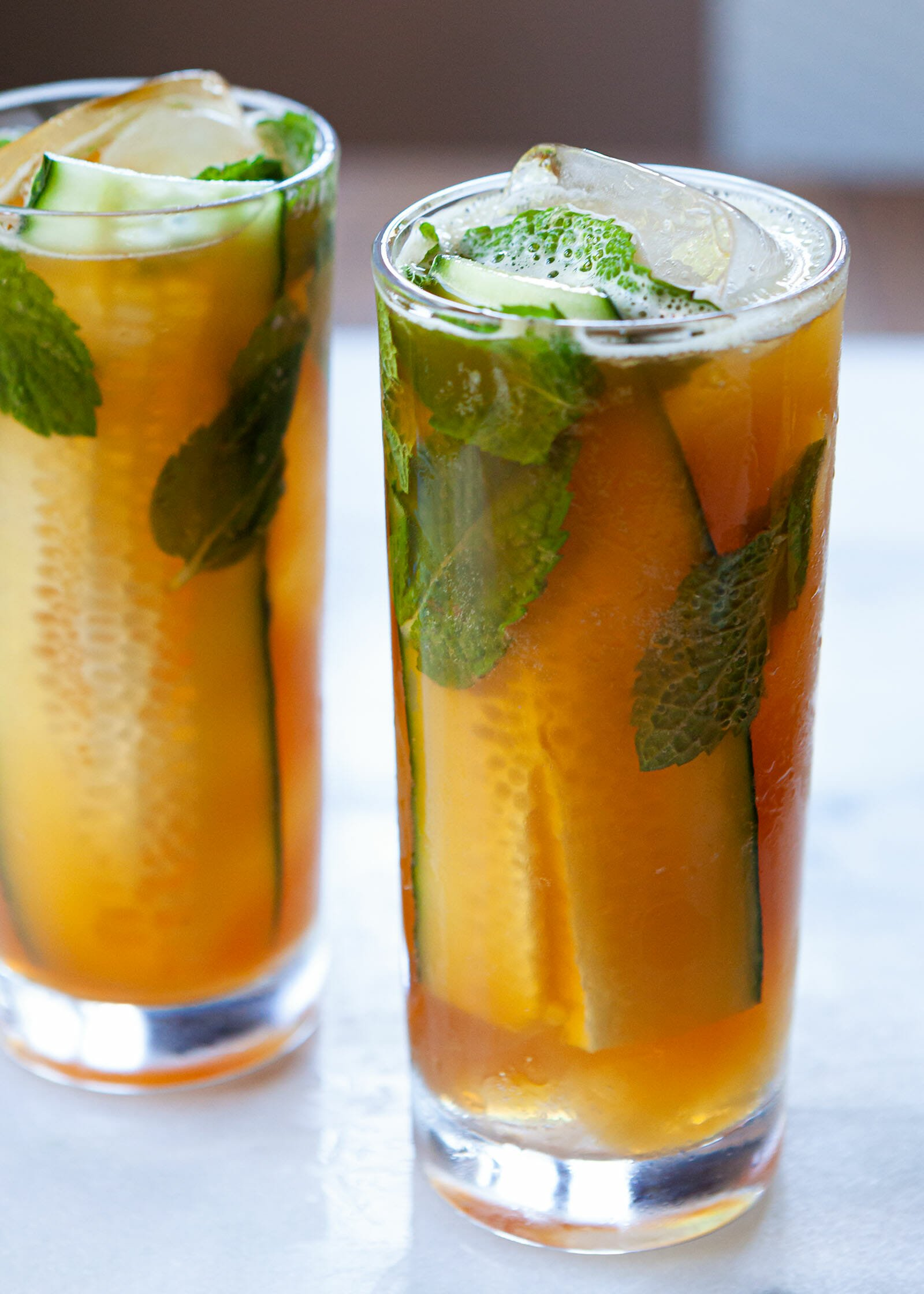 Two highball glasses with Pimm's cup recipe in each. Mint leaves, cucumbers and ice are visible in the glasses.