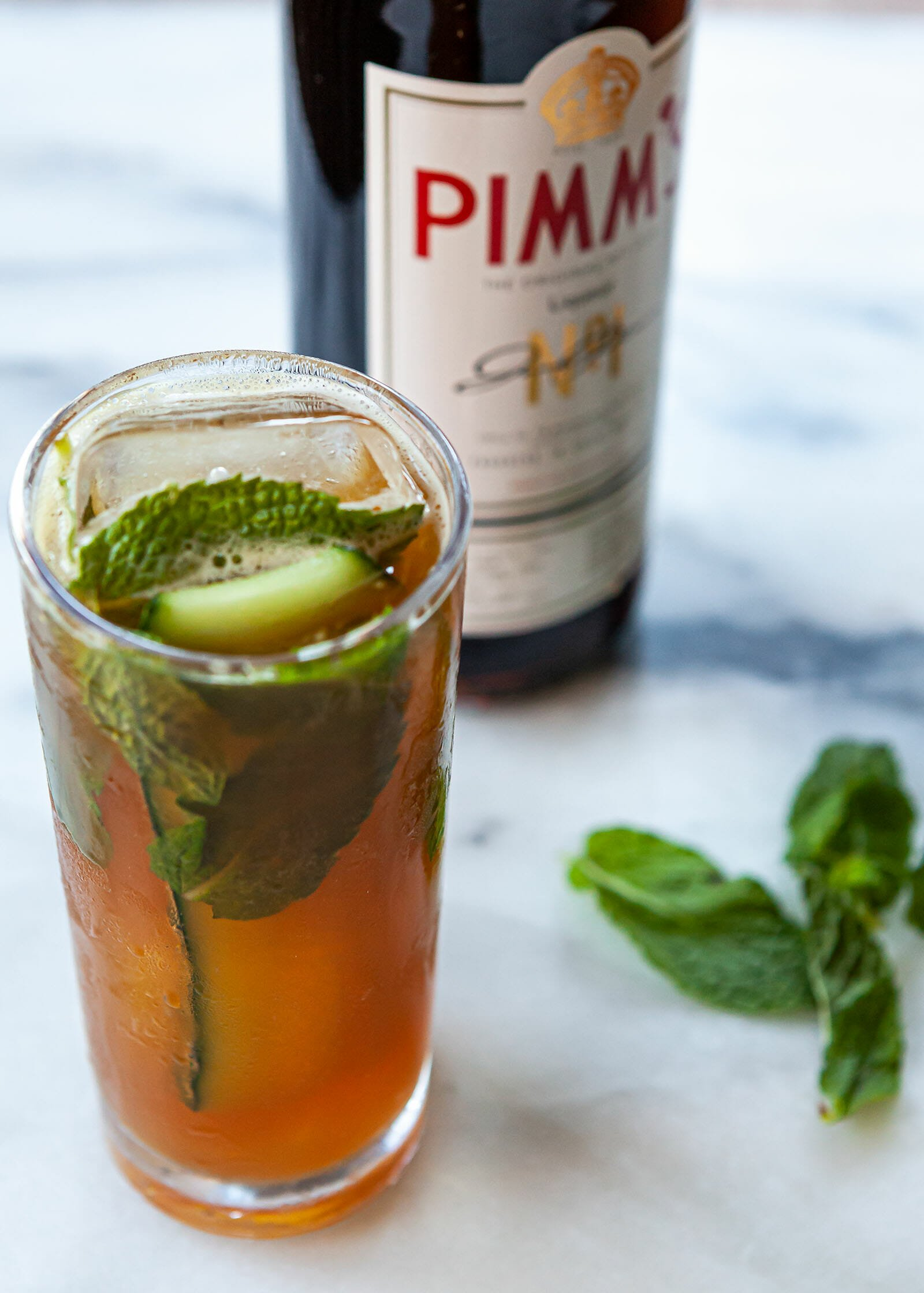 A tall glass with a Pimms cup cocktail is on a counter with mint leaves and a bottle of Pimms no 1 behind it.
