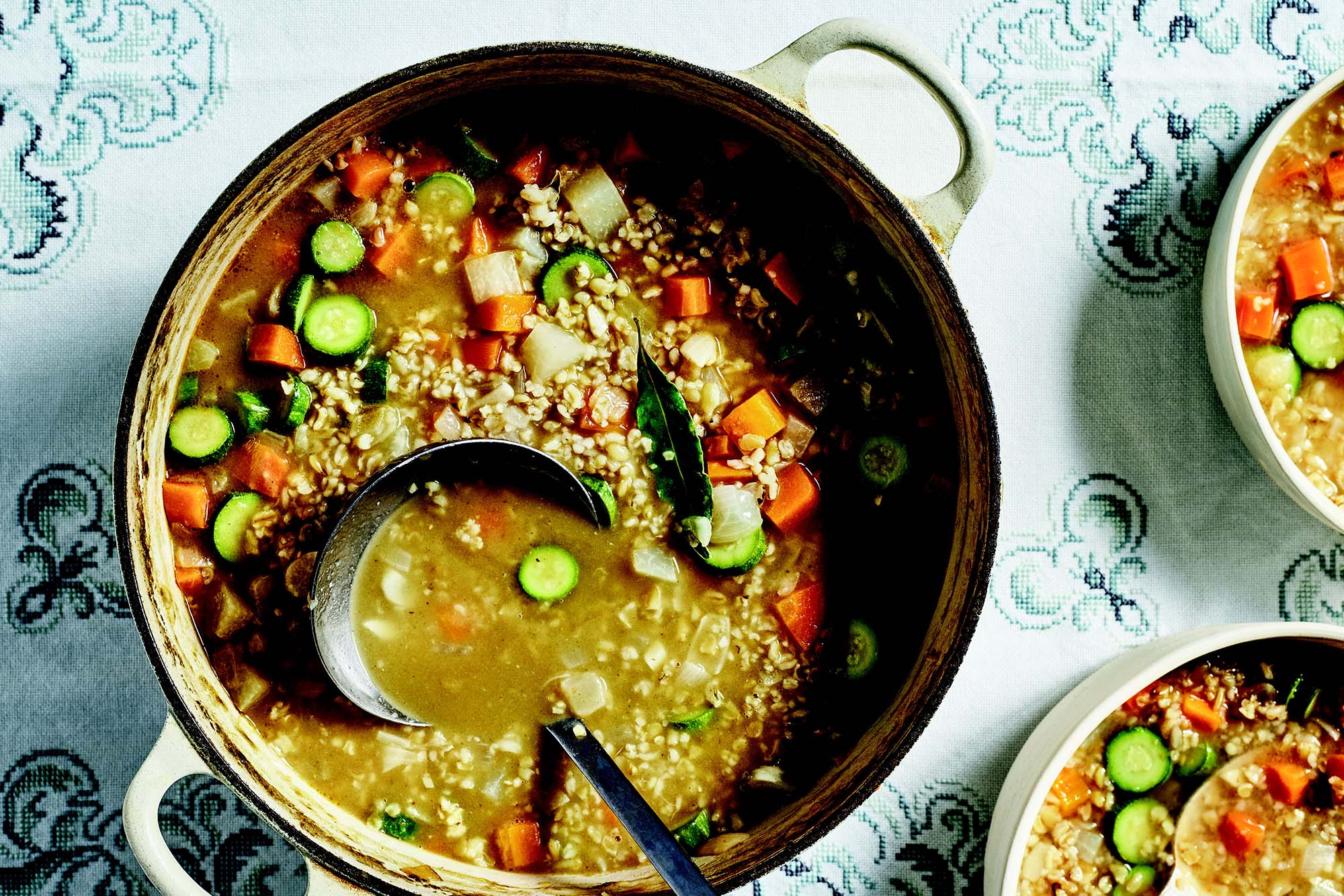 A dutch oven with vegetarian soup with freekeh along with a ladle and two bowls.