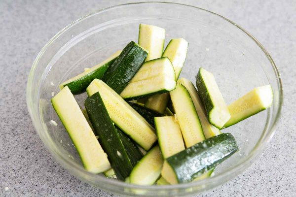 Toss the zucchini with garlic and olive oil in a bowl