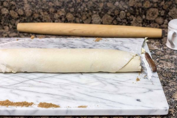 Homemade cinnamon rolls rolled into a long tight spiral and placed on a marble board. A rolling pin is behind the board.