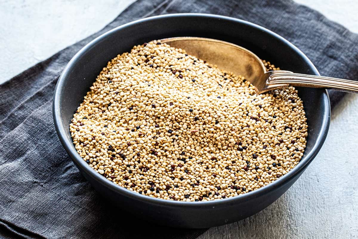 Uncooked quinoa in a blue bowl with a large spoon and a linen underneath to show how to cook fluffy quinoa.