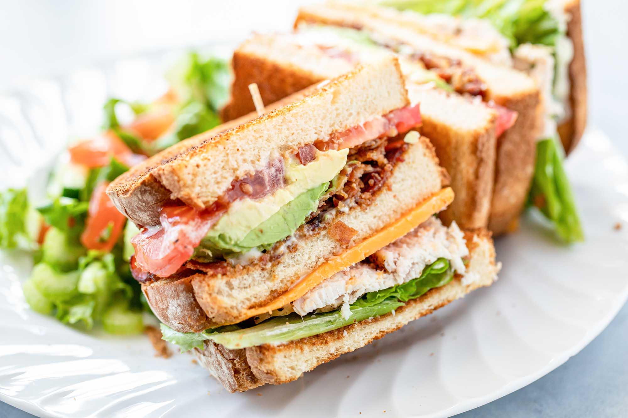 Side view of turkey club with garlic mayo on a plate. The bread is toasted and the mayo, avocado, bacon, tomato, lettuce and turkey are visible in the sandwich.