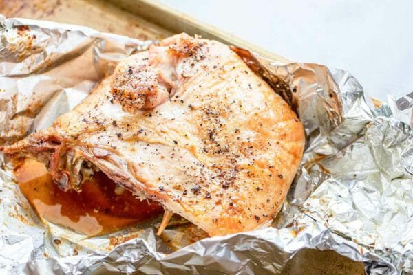 Juicy turkey on a baking sheet with foil underneath to make a homemade turkey club.